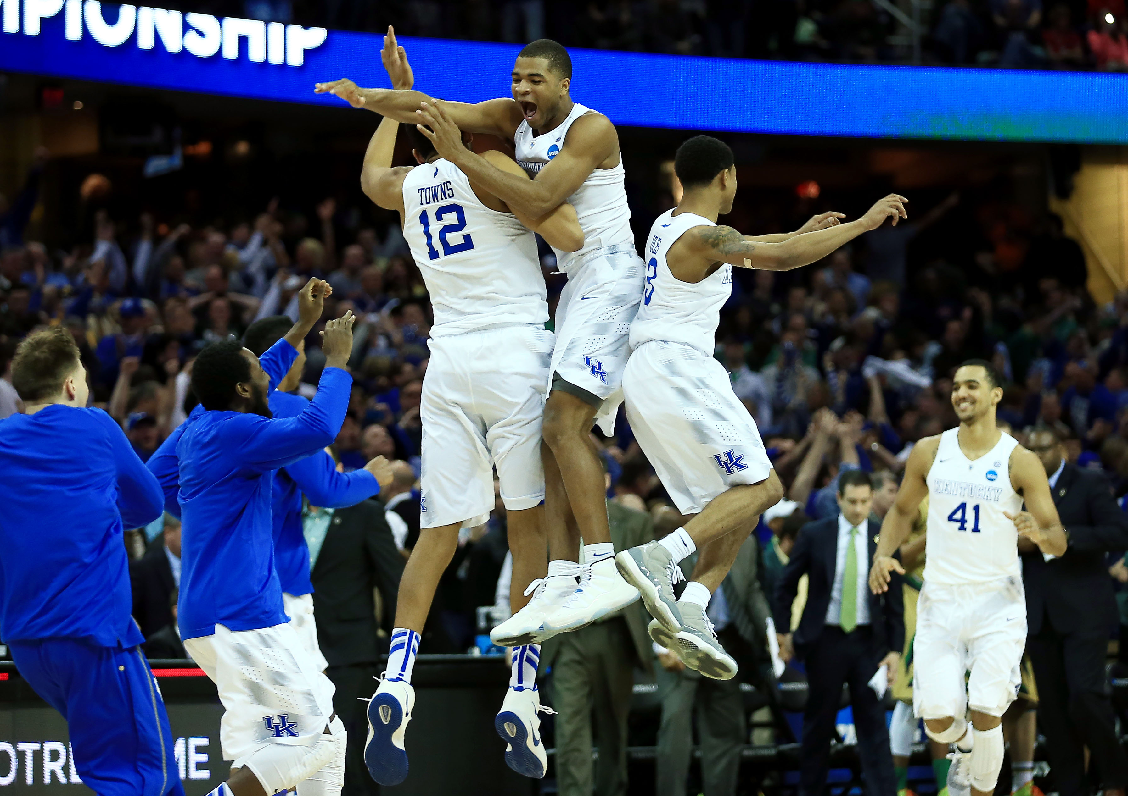 Mar 28, 2015; Cleveland, OH, USA; Kentucky Wildcats forward Karl-Anthony Towns (12) and guard Aaron Harrison (2) and guard Tyler Ulis (3) jump in the air after the game against the Notre Dame Fighting Irish in the finals of the midwest regional of the 2015 NCAA Tournament at Quicken Loans Arena. Kentucky won 68-66. Mandatory Credit: Andrew Weber-USA TODAY Sports